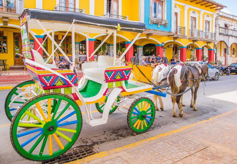 GRANADA, NICARÁGUA, MAIO, 14, 2018: Vista exterior de transportes puxados por cavalos decorados coloridos para o aluguer por turi fotografia de stock royalty free