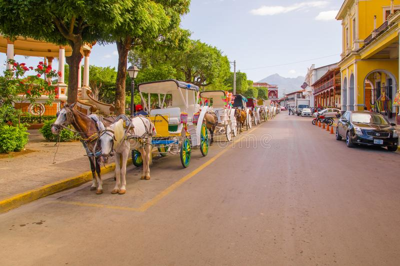 GRANADA, NICARAGUA, MAY, 14, 2018: Outdoor view of colourful decorated horse-drawn carriages for hire by tourists to royalty free stock images