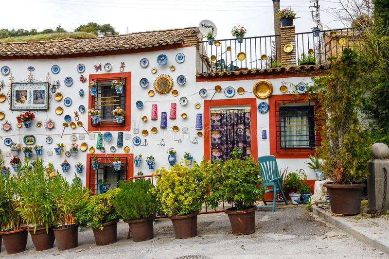 Granada, Spain, April 06, 2018: : Facade of a traditional house with decorative ceramic plates and pots of colorful flowers in the stock photography