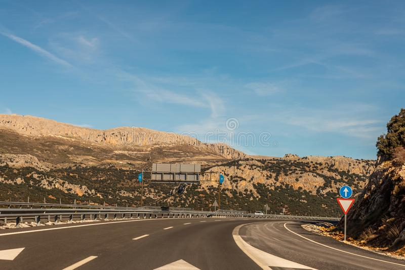 GRANADA SPAIN, DECEMBER 15, 2018 A fast road in the mountains to the city of Granada in Spain, a typical landscape of the region. GRANADA SPAIN, DECEMBER 15 royalty free stock image