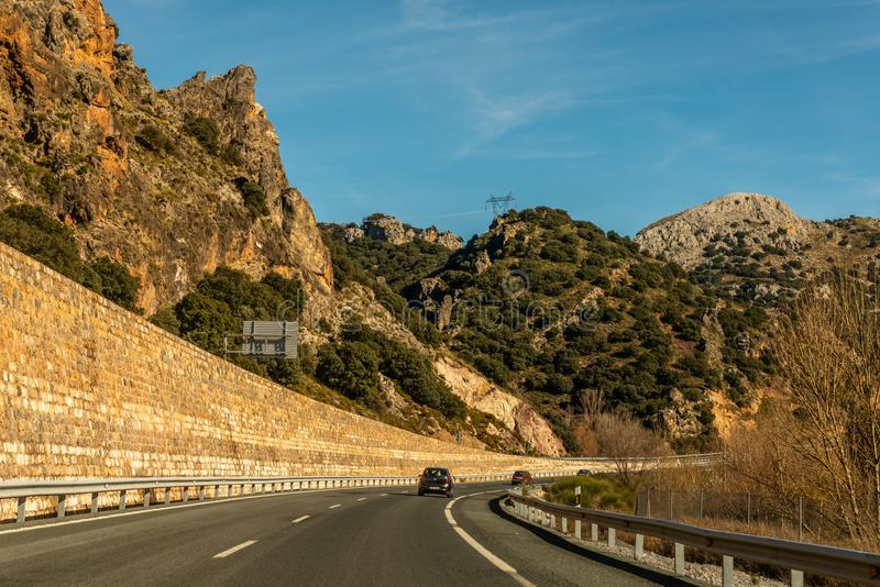 GRANADA SPAIN, DECEMBER 15, 2018 A fast road in the mountains to the city of Granada in Spain, a typical landscape of the region. GRANADA SPAIN, DECEMBER 15 stock photography