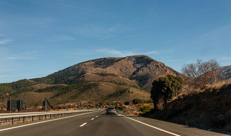 GRANADA SPAIN, DECEMBER 15, 2018 A fast road in the mountains to the city of Granada in Spain, a typical landscape of the region. GRANADA SPAIN, DECEMBER 15 royalty free stock images