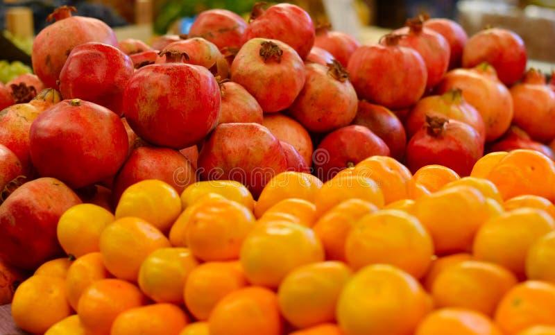 Granadas y mandarinas en el mercado al aire libre imagenes de archivo