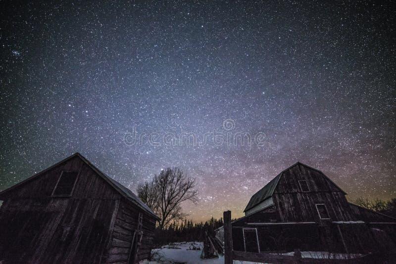 Granai rurali alla notte con le stelle nell'inverno fotografia stock libera da diritti