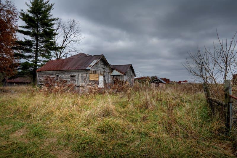 Granaio abbandonato sotto le nubi di tempesta immagine stock