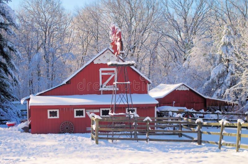 Granaio di cavallo con il mulino a vento coperto di neve immagine stock