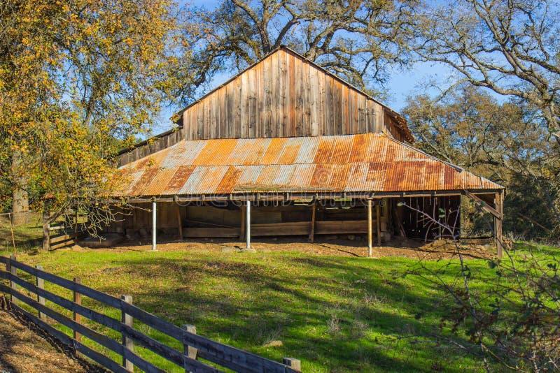 Granaio di legno d'annata con Rusty Tin Roof fotografie stock