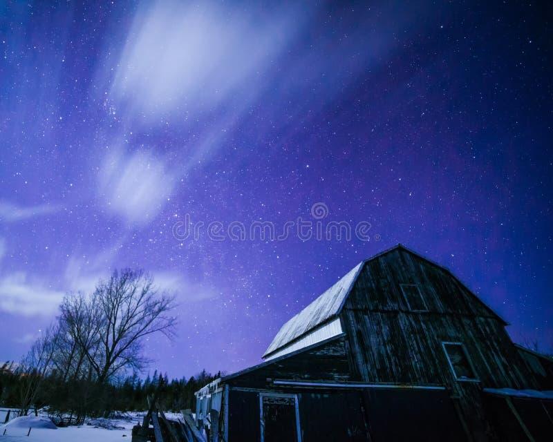Granaio illuminato dalla luna con le stelle e le nuvole nell'inverno immagini stock