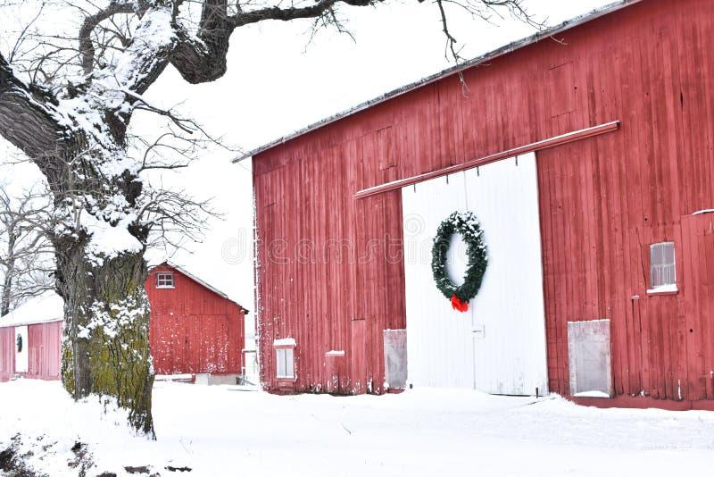 Granaio rosso nell'inverno con una corona di Natale fotografia stock