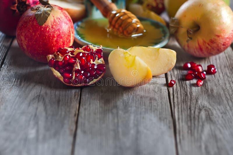 Granatäpple, äpplen och honungbakgrund arkivbilder