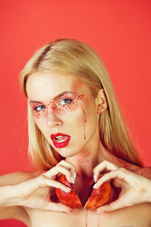 Granatäpple i händer av kvinnan med idérik trendig makeup, vitamin arkivfoto