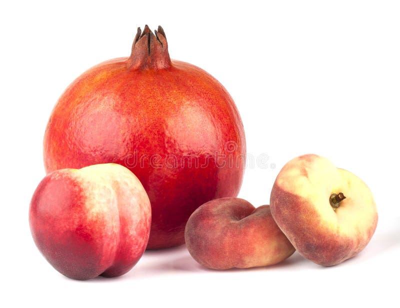 Granatäpple, nektarin och två persikor royaltyfri fotografi