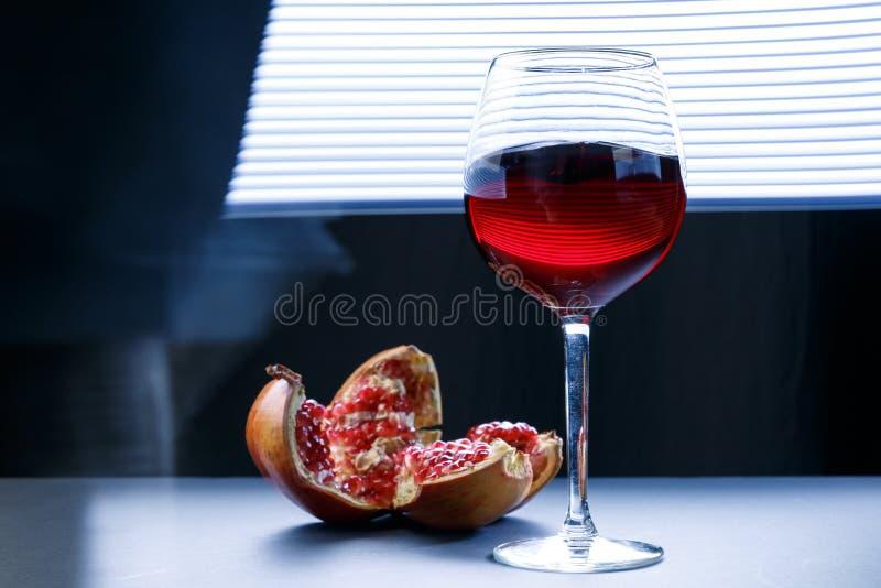 Granatäpplefruktsaft i ett exponeringsglas och några stycken av granatäpplet på en svart bakgrund Vitaminer och mineraler fotografering för bildbyråer