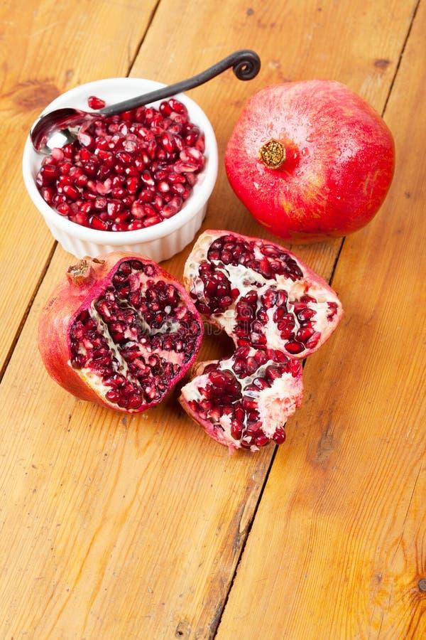 Granatäpplekärnor i en bunke med hel frukt på träyttersida royaltyfri fotografi
