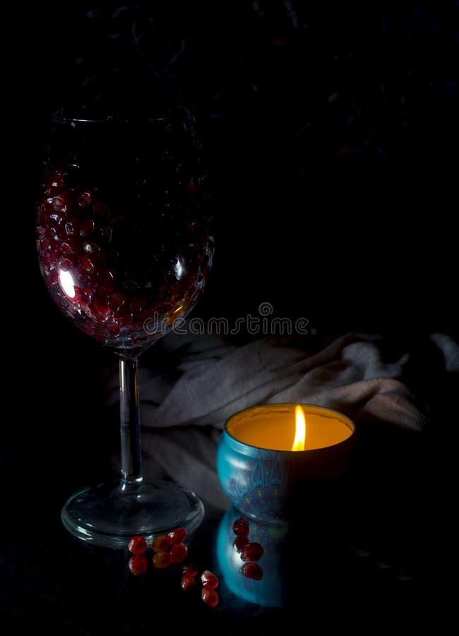Granat?ppleben i ett exponeringsglas med stearinljus i ett m?rkt s?tt arkivbilder