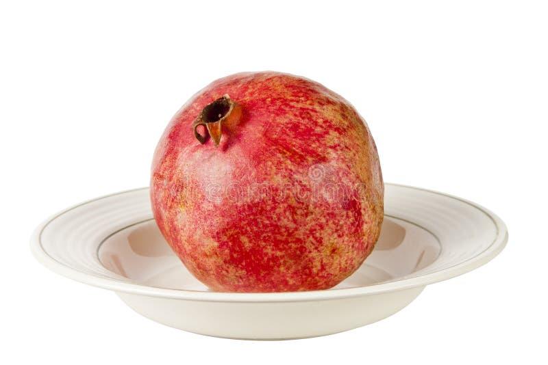 Granatapfel auf einer Platte, lokalisiert auf weißem Hintergrund stockfotos