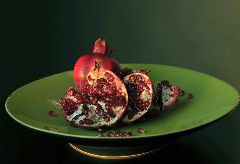 Granatapfel auf grünem Teller lizenzfreie stockfotos