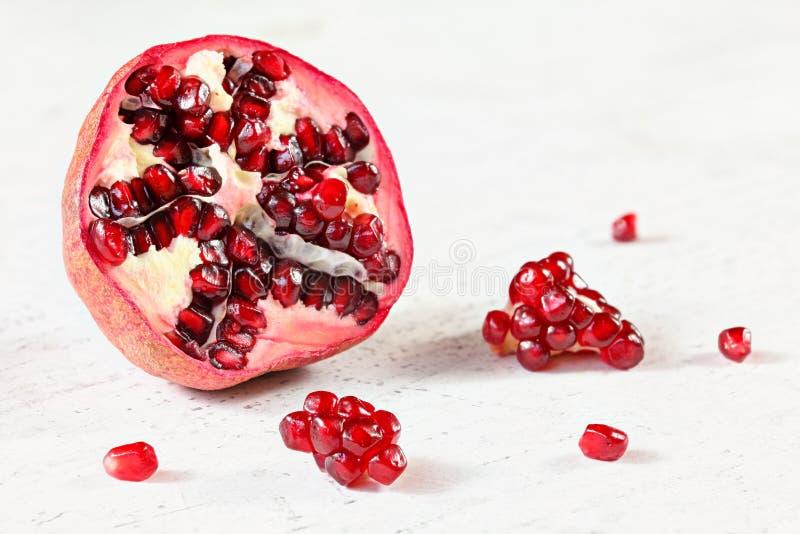 Granatapfel halbiert, wenig Edelstein wie die Fruchtgruppen zerstreut auf weißes Arbeitsbrett nahe bei ihm lizenzfreie stockfotografie