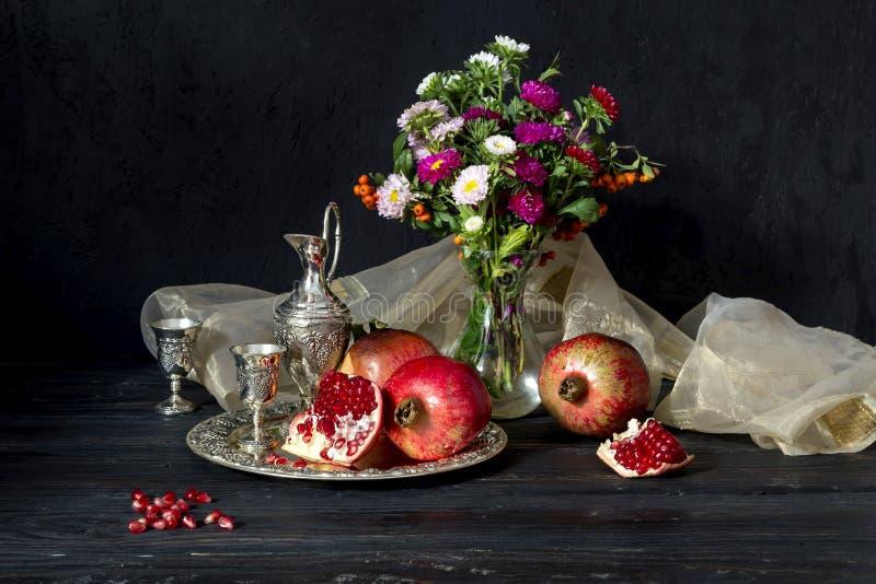 Granatapfel und Stemware mit Likör stockfotos