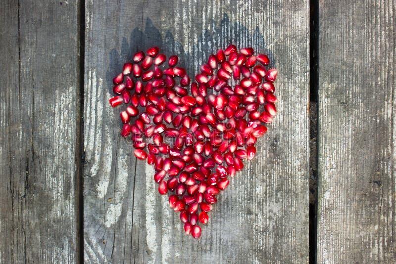 Granatapfelmakrosamen in der Herzform lizenzfreie stockbilder