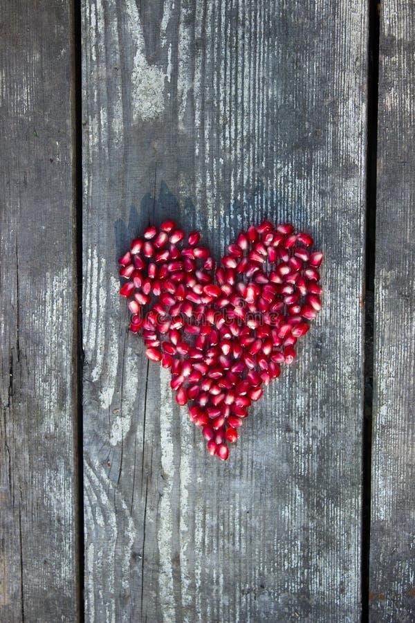 Granatapfelsamen in der Herzform stockbild