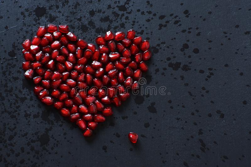 Granatowów ziarna brogują w postaci serca na czarnym tle, kropiącym z wodą zdjęcia stock