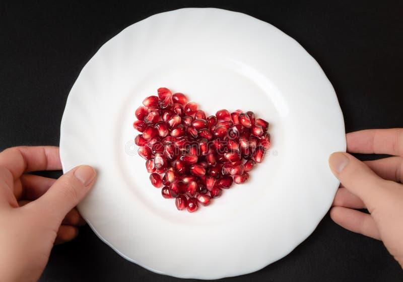 Granatowów ziarna na bielu talerzu serce odizolowane kształtu white pomidorowego zdjęcia royalty free