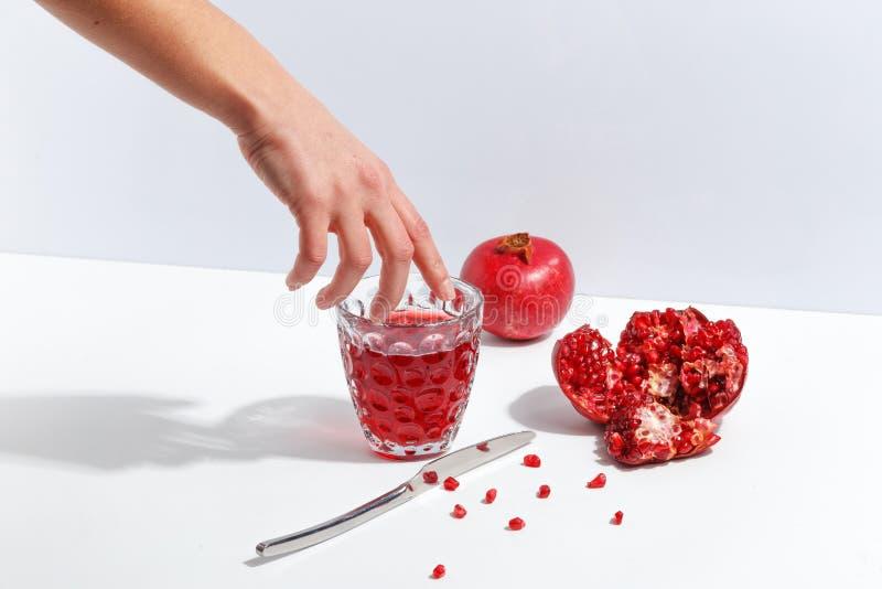 Granatowowie i szkło granatowa sok na białym stole zdjęcia stock
