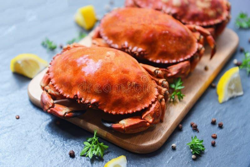 Granchi cucinati sul bordo di legno con il limone sul piatto servito sulla vista superiore del piatto scuro - frutti di mare cott immagine stock