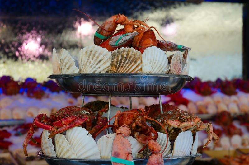 Granchi ed aragoste, decorati con le conchiglie, sul piatto del metallo immagini stock