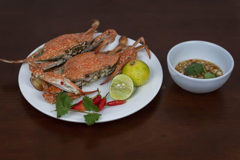 Granchi nuotatori con la salsa di immersione tailandese dei frutti di mare su un piatto fotografia stock libera da diritti