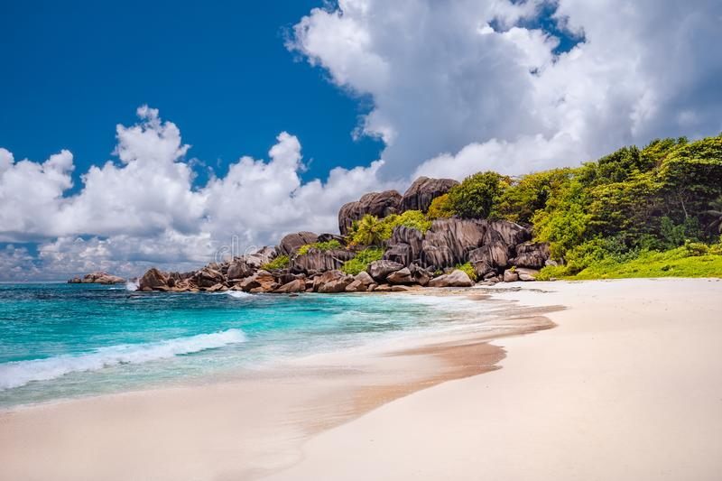 Grand Anse exotic beach at La Digue island in Seychelles. White sandy beach with blue ocean lagoon, white waves and stock photo