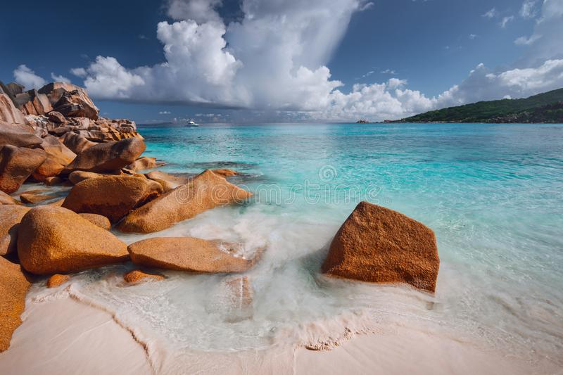 Grand anse, La Digue island, Seychelles. Sandy beach with orange granite boulders and azure ocean lagoon and beautiful. Cloudscape stock photos