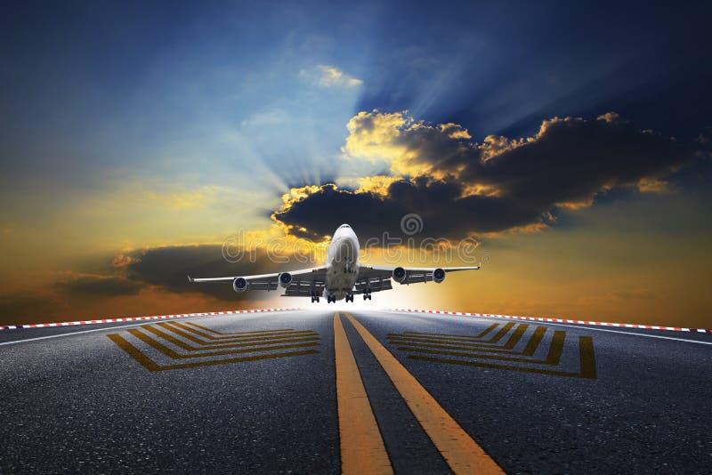 Grand avion de passagers volant au-dessus de la piste d'aéroport image libre de droits