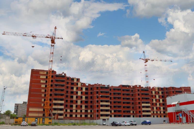 Grand bâtiment résidentiel en construction et deux grues photo libre de droits