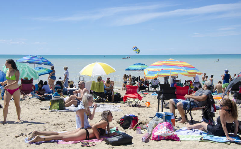 Grand Bend Ontario, Canada - July 02, 2016: Unidentified people. In the beach of the lake Grand Bend in leisure acivities in summertime in a deep blue sky as stock photography
