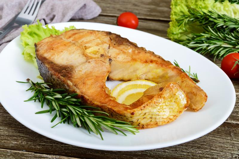 Grand bifteck rôti de carpe avec le citron et le romarin photos stock