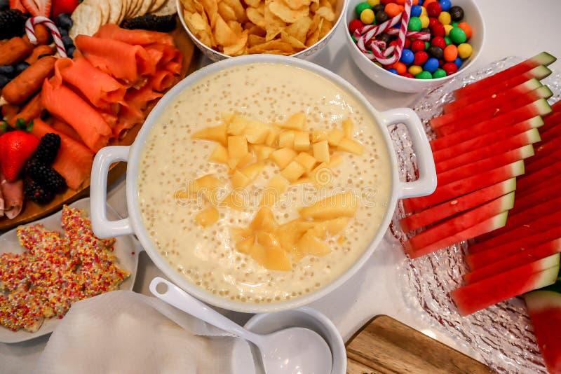 Grand bol de sagou de mangue sur la table de buffet photographie stock