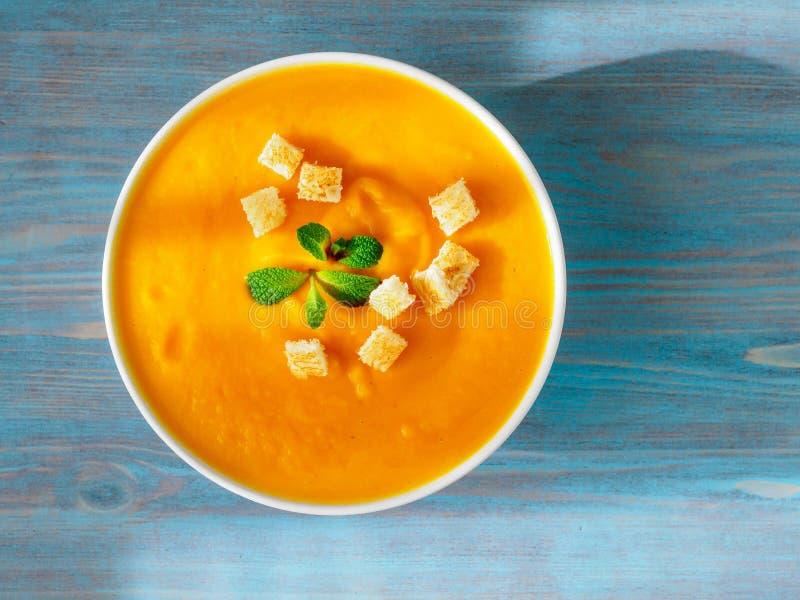 Grand bol de soupe à potiron sur un fond bleu en bois TAS lumineux photo stock