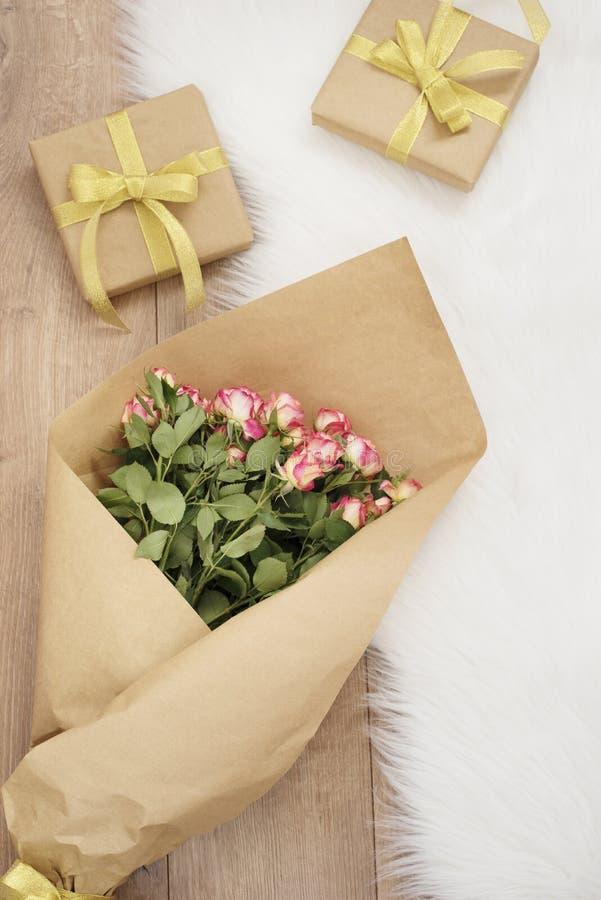 Grand bouquet de luxe des roses et des cadeaux sur un tapis de fourrure images libres de droits