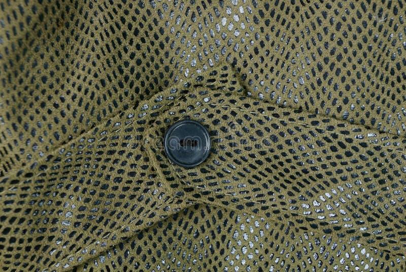 Grand bouton noir sur la robe en cuir inégale images stock