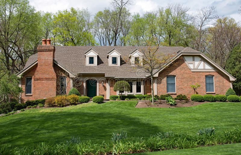 Grand Brick Home with Landscaped Lawn. Grand red brick home in early spring with well maintained lawn royalty free stock photography