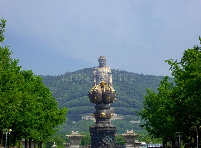Grand Buddha Sculpture with Bathing by nine dragons in the front. A giant bronze Grand Buddha statue with blue sky and white clouds background, Bathing by nine stock images