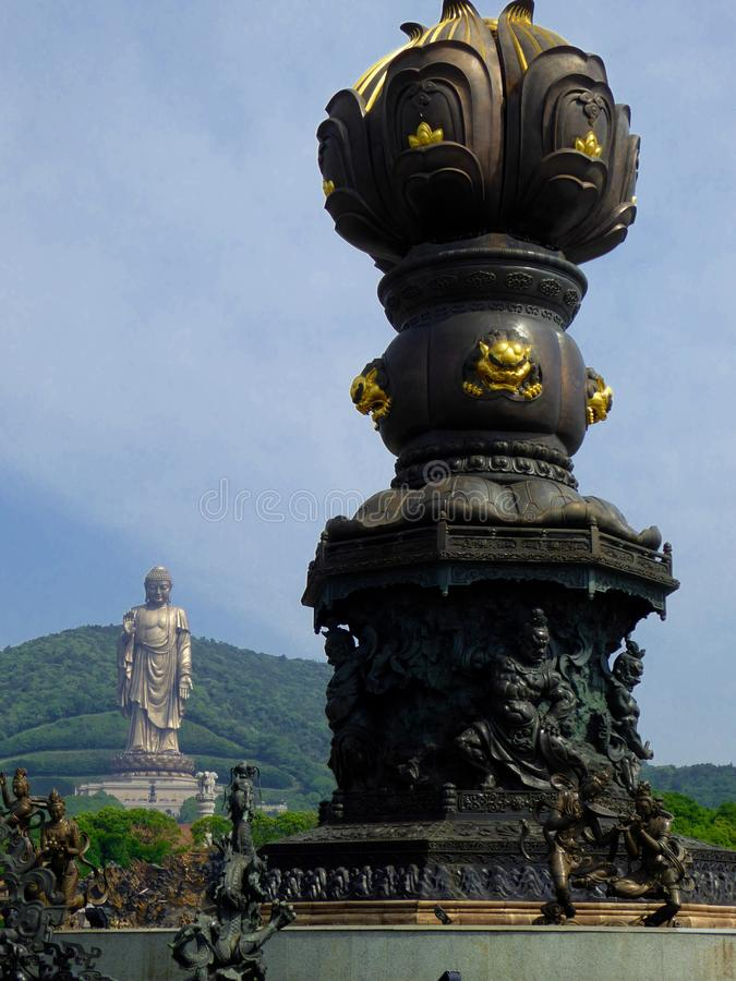 Grand Buddha Sculpture with Bathing by nine dragons in the front. A giant bronze Grand Buddha statue with blue sky and white clouds background,Bathing by nine stock photography