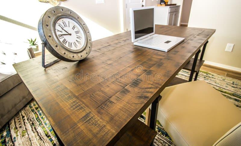 Grand bureau en bois avec l'horloge et l'ordinateur portable photo stock