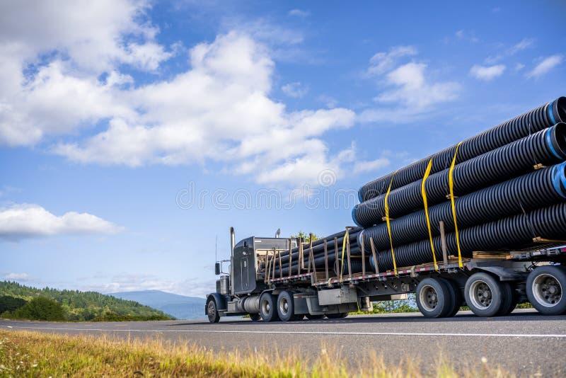 Grand camion à grande capacité noir semi-remorque transportant des tuyaux en plastique fixé sur une semi-remorque descendante cir images stock