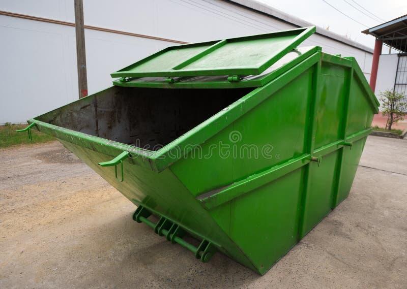 Grand camion à ordures vert de décharge sur la route dans l'usine, vue de côté photo stock