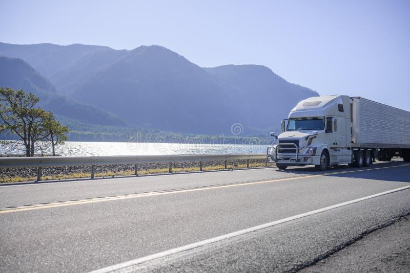 Grand camion à semi-remorque blanc avec dispositif de protection à grilles dans une semi-remorque réfrigérée circulant sur la rou photos libres de droits