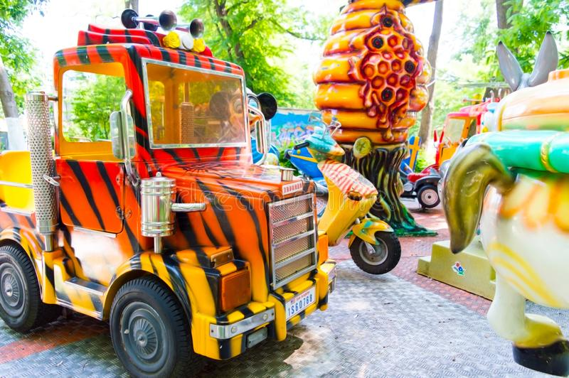 Grand camion sur un carrousel d'enfants en parc d'attractions images libres de droits