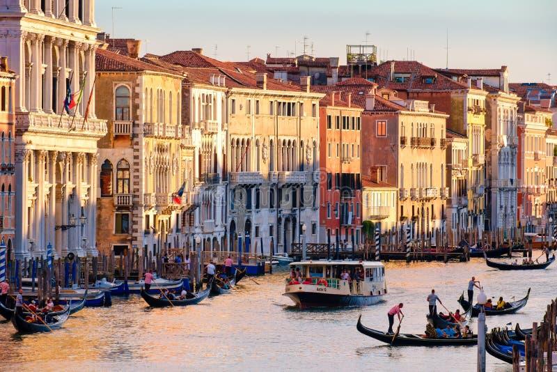 Grand Canal en Venecia en la puesta del sol con las góndolas y los edificios coloridos viejos fotografía de archivo
